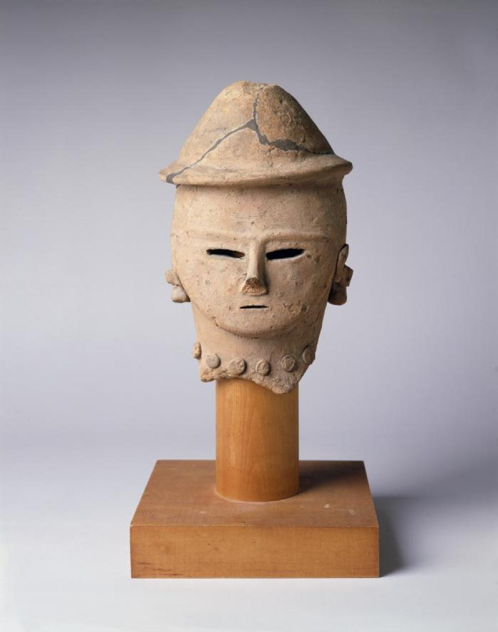 Japanese; Head of Haniwa Figure; Tumulus Period, 5th-6th century; Earthenware, wood base; 6 1/8 x 4 1/4 x 5 in., base 6 /14 x 6 in.; Private collection. (Study Collection; Collectibles, C-S-47)
