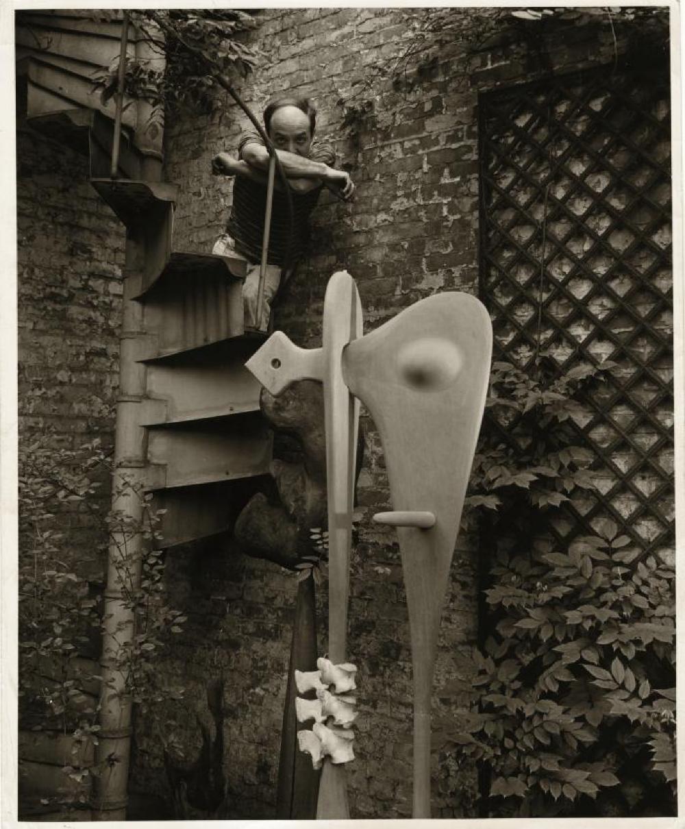 "Isamu Noguchi in the courtyard of his MacDougal Alley Studio with ""Bone Sculpture"""
