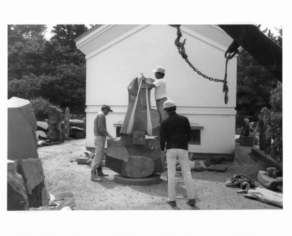 Workers moving a large sculpture in the yard of Isamu Noguchi's studio in Mure, Japan
