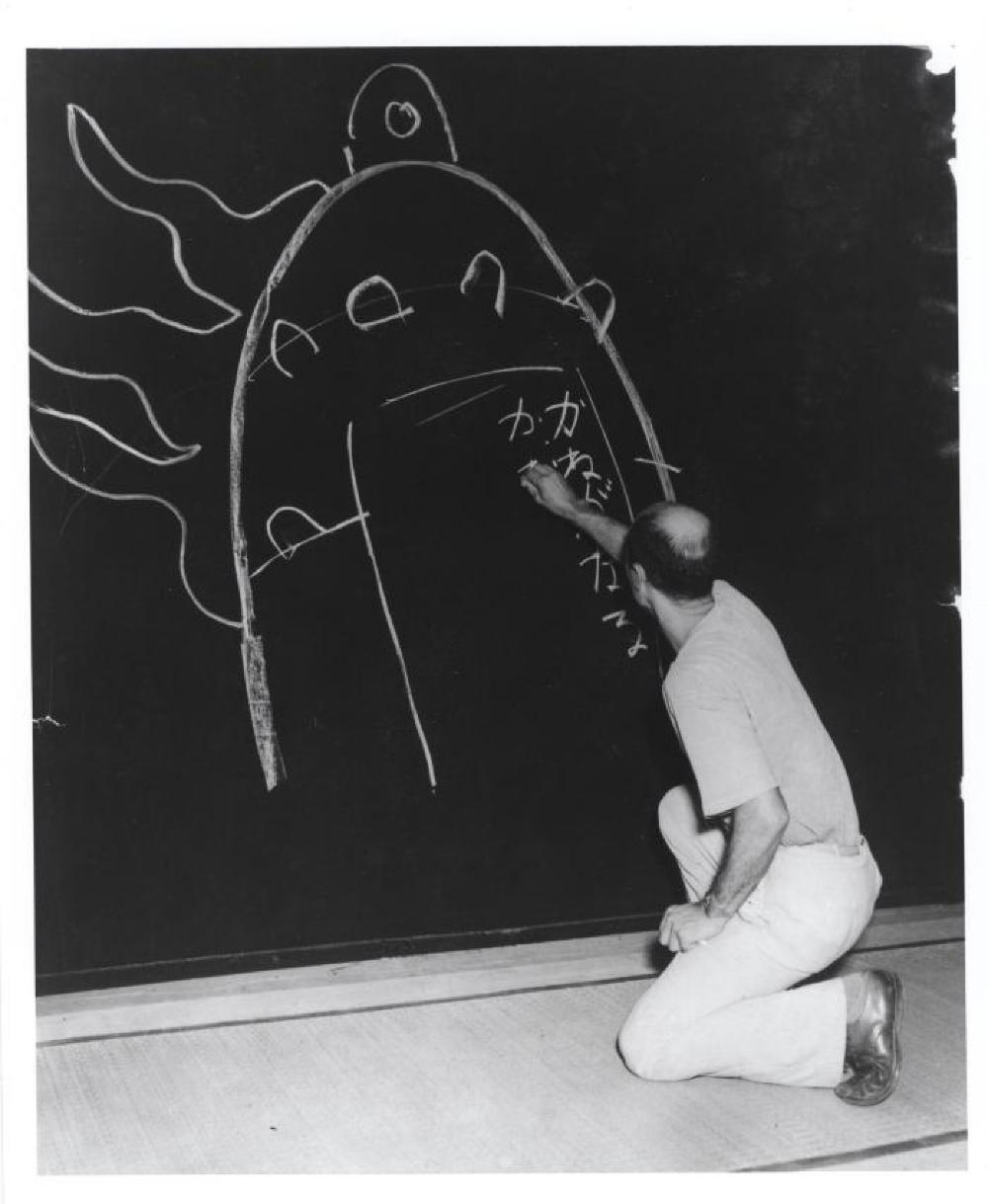 "Isamu Noguchi writing his father's poem ""Kane ga naru"" at his exhibition at Mitsukoshi Department Store, (Nihombashi Head Store), Tokyo,  August 1950"