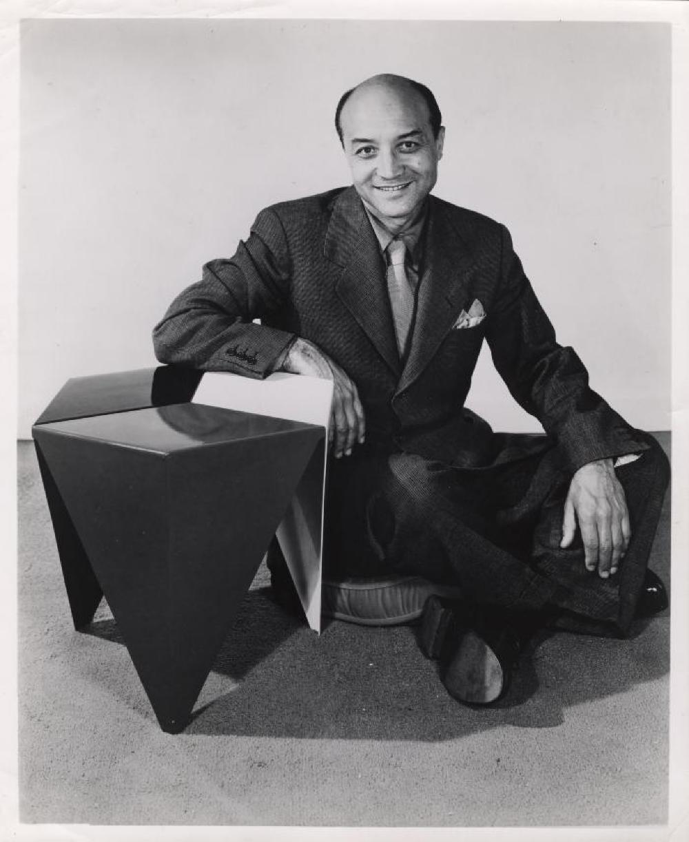 Isamu Noguchi with Prismatic Table in publicity shot for Alcoa