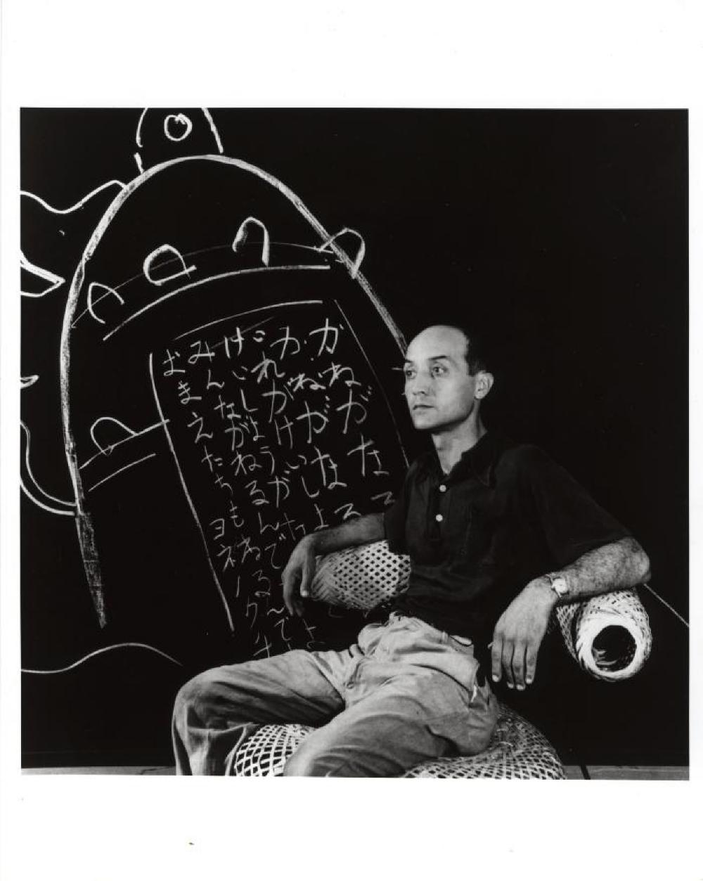 Isamu Noguchi seated in Basket Chair, with writing of his father's poem at the Mitsukoshi Dept Store exhibition, Aug. 1950.