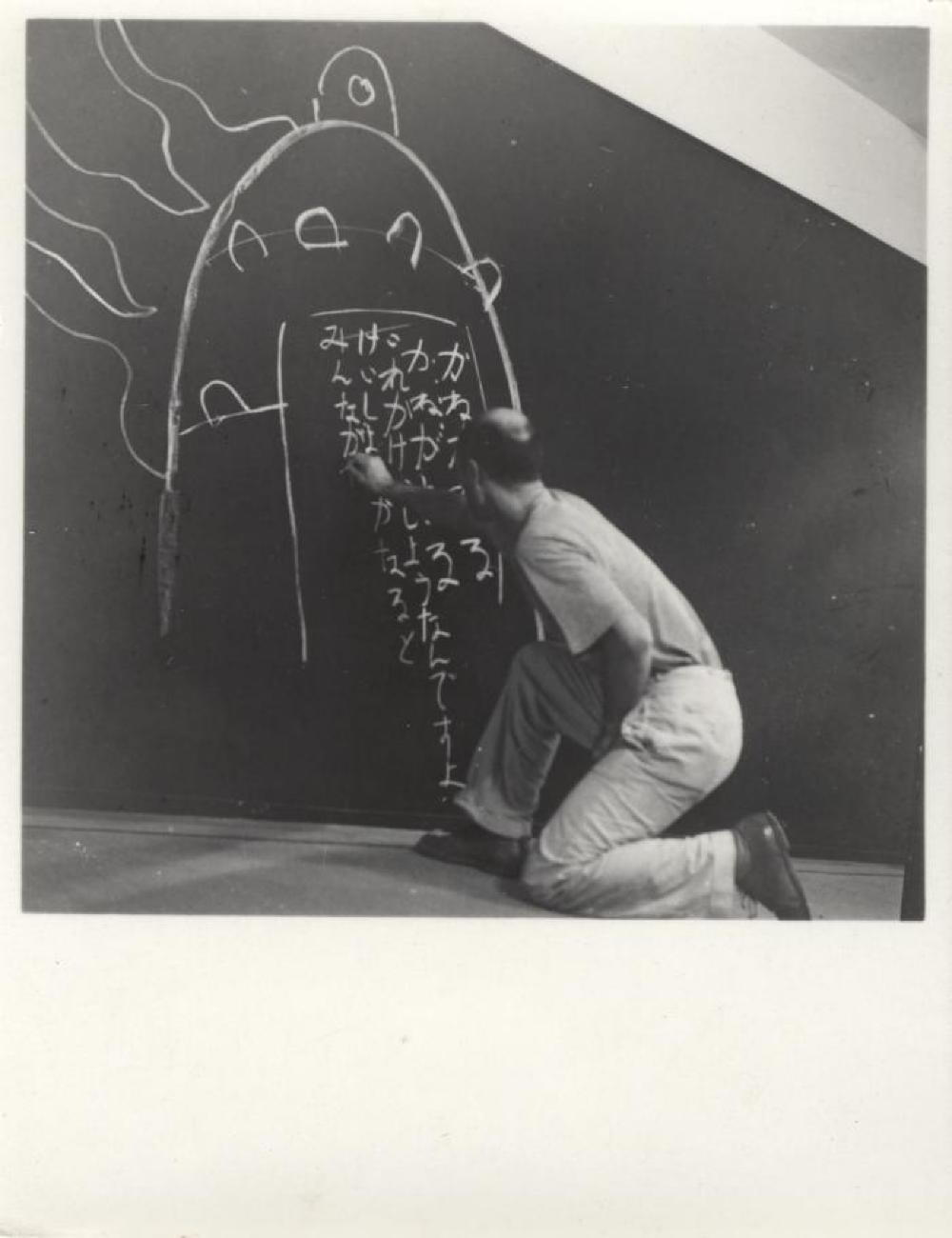 "Isamu Noguchi writing his father's poem ""Kane ga naru"" at his exhibition at Mitsukoshi Department Store, Tokyo,  August 1950"
