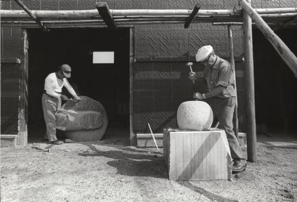 """Isamu Noguchi and assistant at work on """"Childhood"""" and """"The Seeker Sought"""" at his studio in Mure (Shikoku, Japan)"""