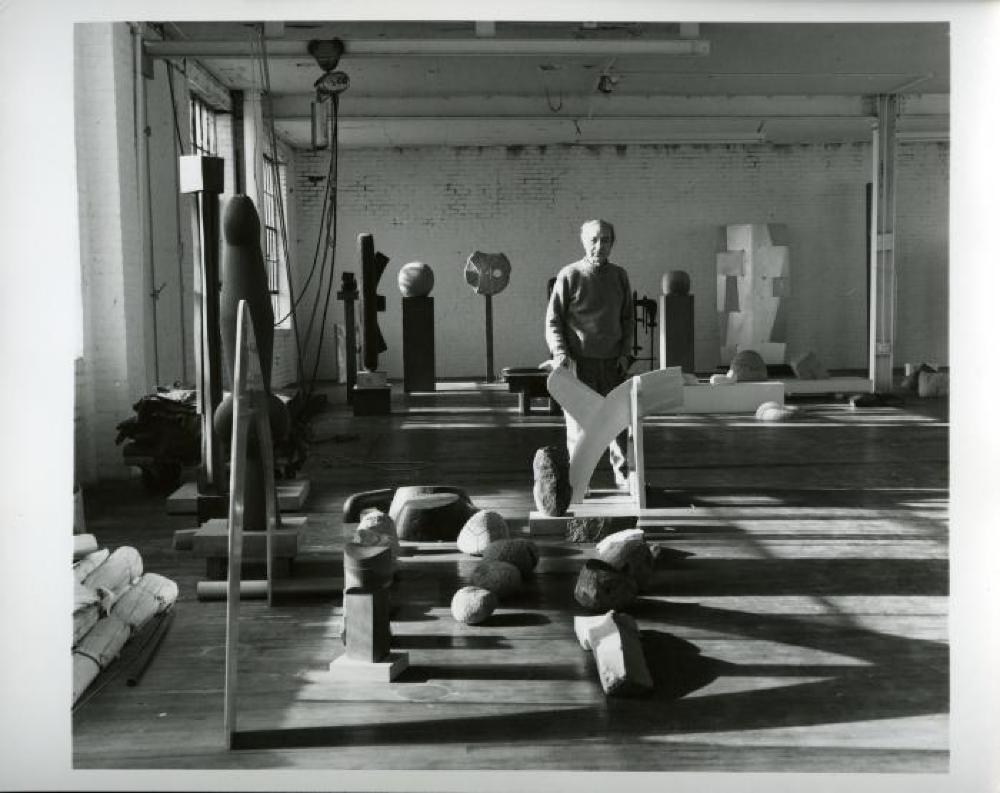 Isamu Noguchi with sculptures in his Long Island City storage space